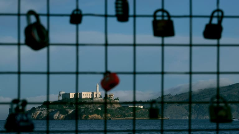 Alcatraz Island is shown behind a locks on a pier fence in San Francisco. Some tours to the island have stopped because the ferry is government-run.