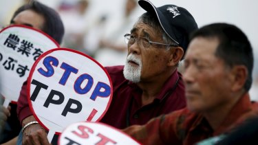 Japanese farmers hold placards opposing the Trans-Pacific Partnership in Tokyo.