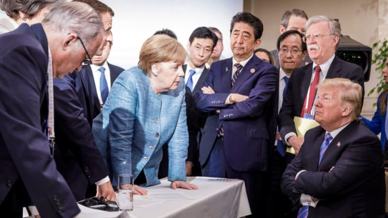 German Chancellor Angela Merkel, centre, speaks with US President Donald Trump during the G7 Leaders Summit.
