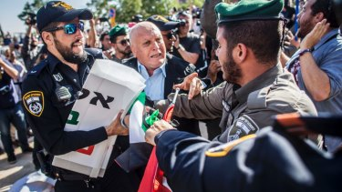 Israeli border police officer pulls a sign from a Palestinian protester outside the new US Embassy in Jerusalem.