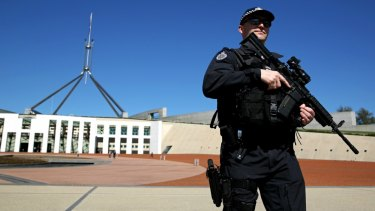 Australian Federal Police officers patrol the front of Parliament House in Canberra.