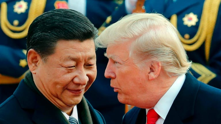 U.S. President Donald Trump, right, chats with Chinese President Xi Jinping during a welcome ceremony at the Great Hall of the People in Beijing.