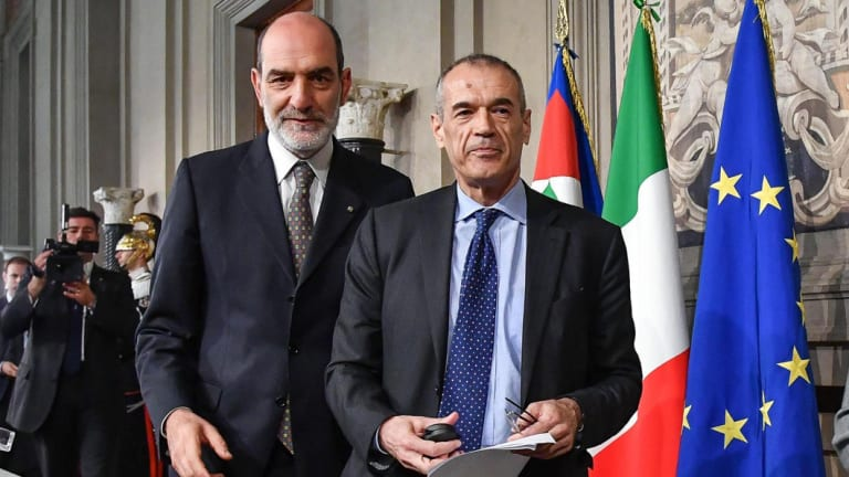 New premier-designate Carlo Cottarelli, right, arrives to address the media after meeting with Italian President Sergio Mattarella.