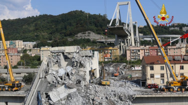 Firefighters remove rubble of the collapsed Morandi highway bridge, in Genoa, Italy, on Saturday.