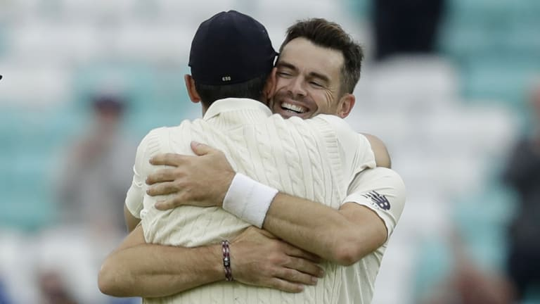 Jimmy Anderson celebrates his record-breaking wicket with friend and teammate Alastair Cook.