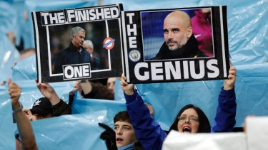 No contest: Manchester City supporters hold up pictures of Mourinho and City coach Pep Guardiola.