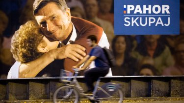 A cyclist rides past a campaign poster of Slovenian President Borut Pahor, in Ljubljana.