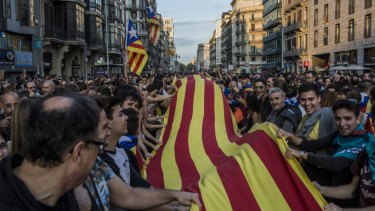 Demonstrators wave a large Catalan flag while marching through Barcelona in October.