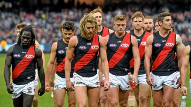 Dejected: Essendon players trudge off the ground after their round 8 loss to Carlton.