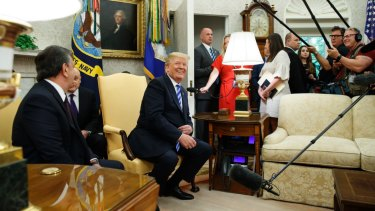 President Donald Trump laughs during a meeting with Uzbek President Shavkat Mirziyoyev in the Oval Office of the White House in May.
