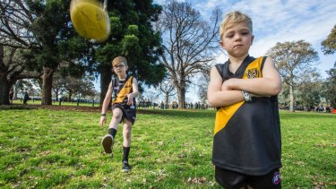 Hendrix, 8, kicks the ball while his brother Tyler stands by as they wait to go into the MCG on Saturday.