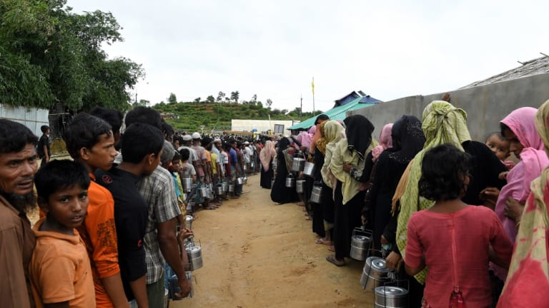 Rohingya refugees queue for a meal provided by an aid agency in Bangladesh. Some 600,000 Rohingya have fled Myanmar since the crack down in 2017.