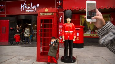 A boy poses for a photo outside of Hamleys toy store in Beijing. The store is twice the size of the British toy retailer's flagship London location.