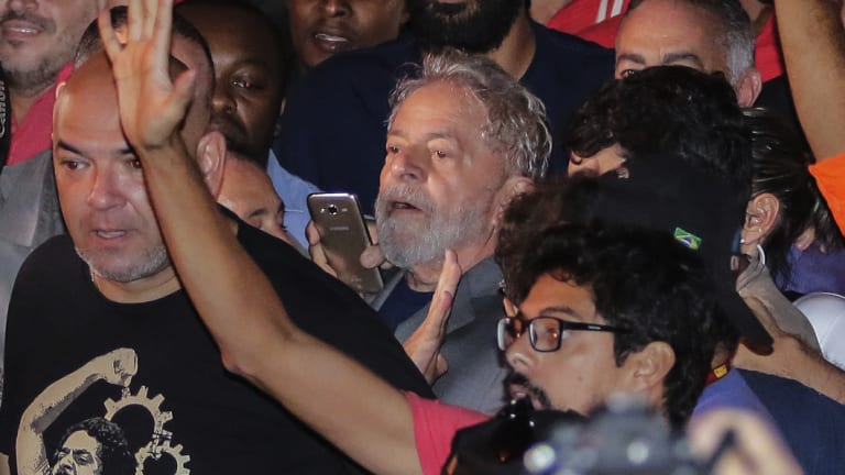 Former Brazilian president Luis Inacio Lula da Silva, centre, leaves the metal workers union headquarters before his arrest.