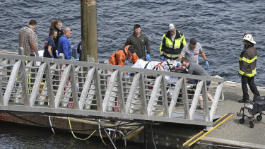 Emergency response crews transport an injured passenger to an ambulance at the George Inlet Lodge docks in Ketchikan, Alaska, on Monday.