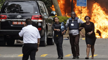 Security forces help civilians flee the scene as cars burn after an upscale hotel was attacked in Nairobi.