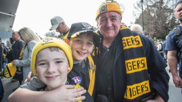 Richmond supporters Mitch Humphries and Liam James wait in line at the MCG with their great uncle Syd James.
