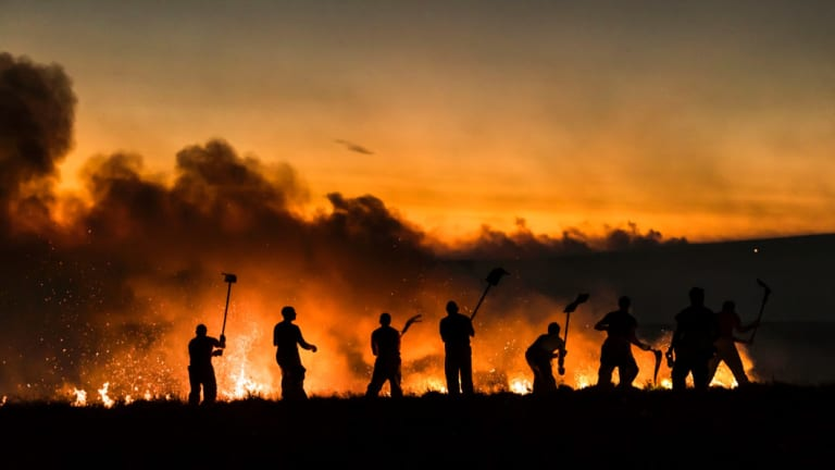 Firefighters work on a wildfire on Winter Hill near Bolton, England.  Extreme temperatures, particularly warm ones, have again been prominent in 2018, on course to be one of the hottest years in history.