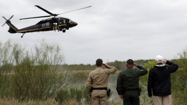 President Donald Trump salutes as a US Customs and Border Protection helicopter passes in McAllen, Texas.