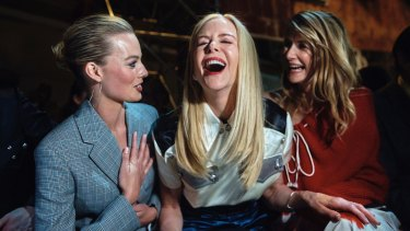 Margot Robbie, left, Nicole Kidman, center, and Laura Dern, right, laugh during the Calvin Klein fashion show in 2018.