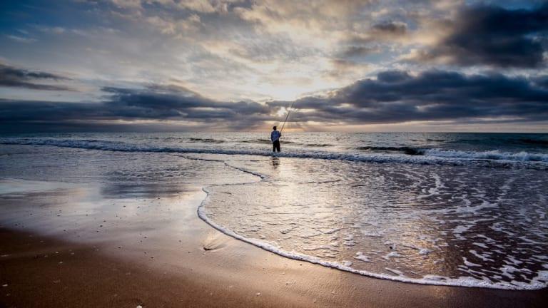 A fisherman at dawn on Paradise Beach.