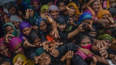 Rohingya Muslim women, who crossed over from Myanmar into Bangladesh, stretch their arms out to collect sanitary products.