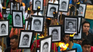 Family members of 43 missing teacher's college students carry pictures of the students in a 2016 protest against closing the case.