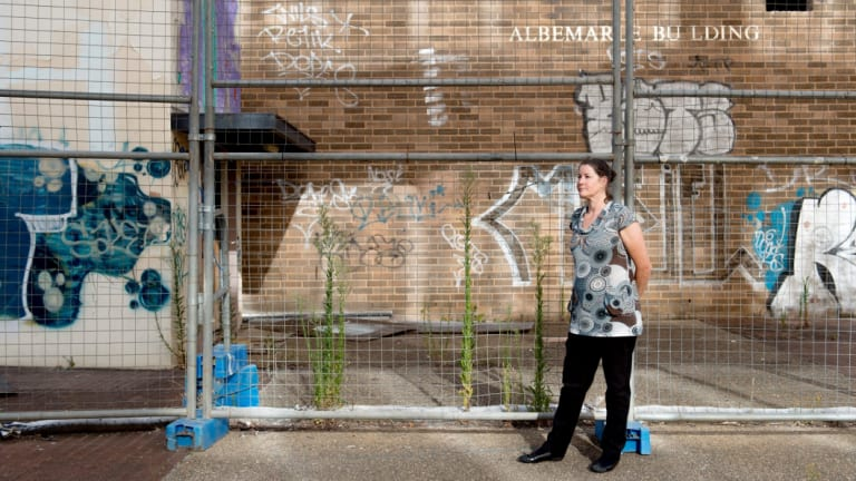 Woden Valley Community Council president Fiona Carrick in front of some of Woden's derelict buildings. The Woden community is banking on light rail for urban renewal.