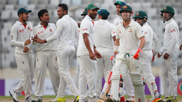Over and out: David Warner walks after being dismissed by Bangladesh's Mehedi Hasan Miraz, second left, on day one of the first Test.