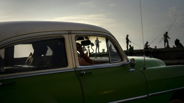 A couple in a classic American car drive along the Malecon seawall past fishermen at sunset in Havana, Cuba.