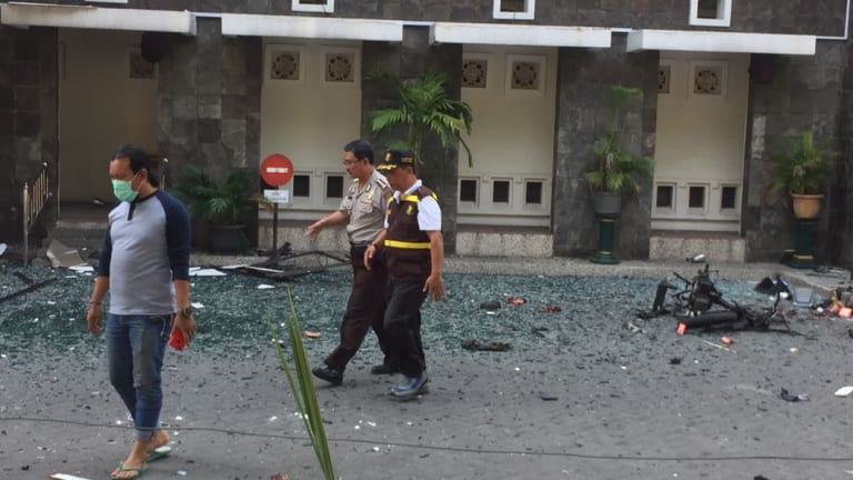 Officers walk past debris at Santa Maria church in Surabaya.