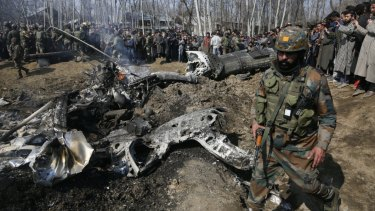 An Indian army solider walks past the wreckage of an Indian aircraft after it crashed in the outskirts of Indian controlled Kashmir.