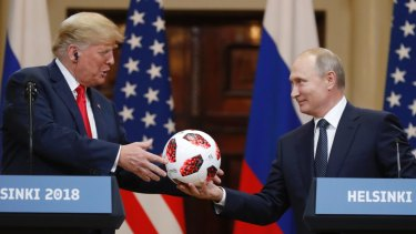 Russian President Vladimir Putin gives a soccer ball to US President Donald Trump in Helsinki, Finland. Trump said he believed Putin's denial of meddling in the elections.