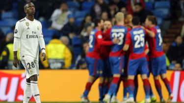 Real Madrid forward Vinicius Junior looks on as CSKA players celebrate.