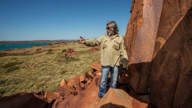 Jakari Togo, a senior cultural ranger at Murujuga National Park, looks out to sea next to rock carvings on the Burrup Peninsula.