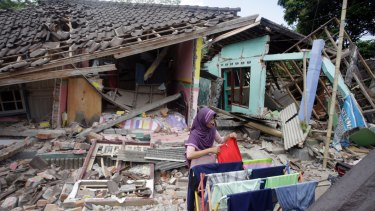 A woman dries her laundry in front of her home destroyed in an earthquake earlier this month.