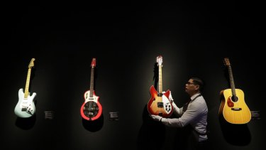 A technician arranges guitars from the collection of David Gilmour, guitarist, singer and songwriter of Pink Floyd, during a press opportunity at Christie's auction rooms in London.