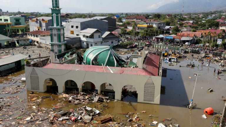 People survey the mosque damaged following earthquakes and tsunami in Palu, Central Sulawesi.