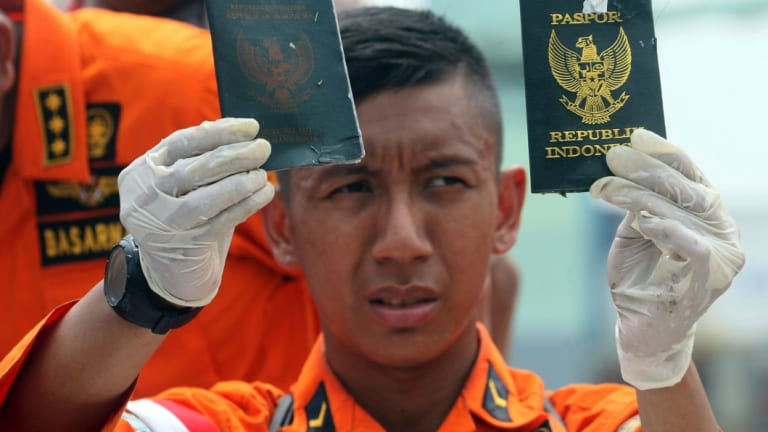 A rescuer shows passports recovered from the area where a Lion Air plane is suspected of crashing.