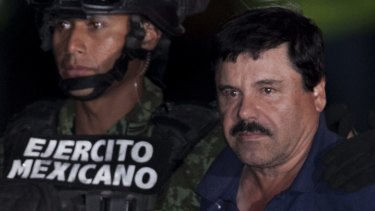 """Mexican drug lord Joaquin """"El Chapo"""" Guzman, right, is escorted by soldiers and marines to a waiting helicopter in Mexico City in 2016."""