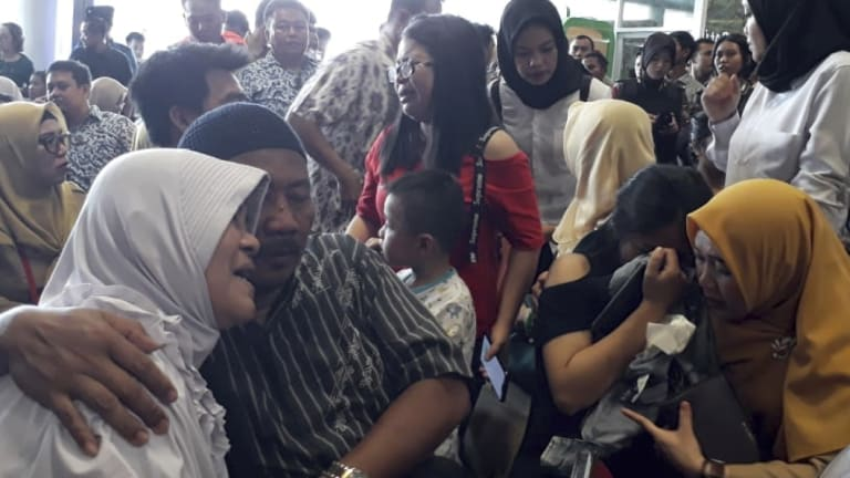 Relatives of passengers comfort each other at Depati Amir Airport in Pangkal Pinang as they wait for news on a Lion Air plane that crashed off Java Island.