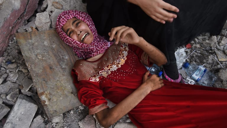 Fifteen year old Tabarek who is wounded and can no longer walk lies at the feet of her family as they rest for a few moments before making their way along a safe corridor during the offensive to retake West Mosul.