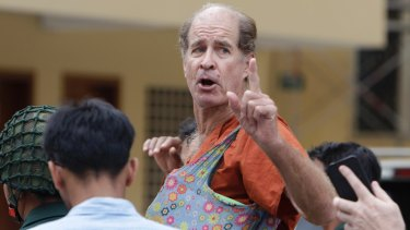 Australian filmmaker James Ricketson gestures as he is escorted by prison guards in January.