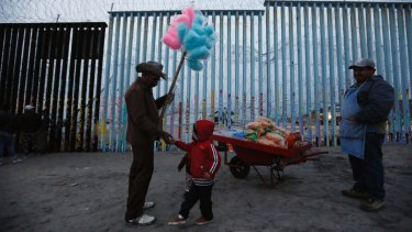 A Honduran migrant boy tries to buy cotton candy from a vendor, but doesn't have enough money, as migrants visit the US border wall to look for opportunities to cross at the beach in Tijuana, Mexico.