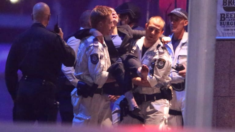 A woman is carried away from the Lindt cafe siege in Sydney's Martin Place in 2014.