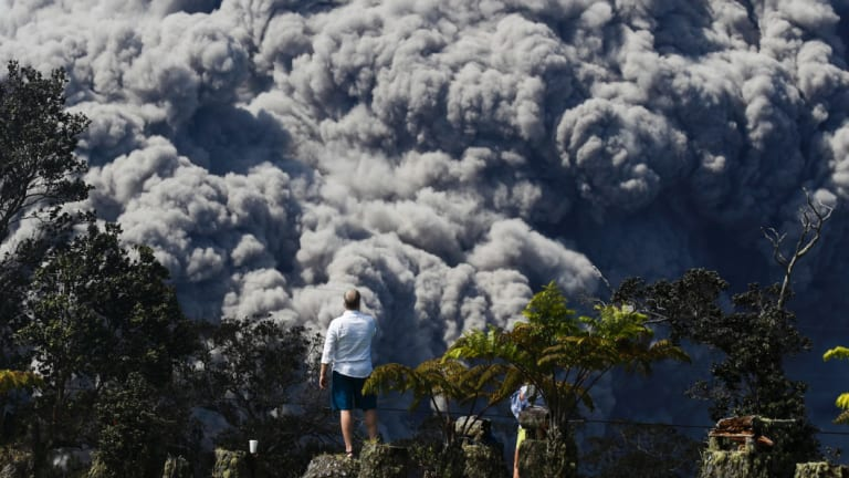 Jack Jones at a country club in Volcano, Hawaii, as a huge ash plume rises from the summit of Kiluaea volcano on May 21.