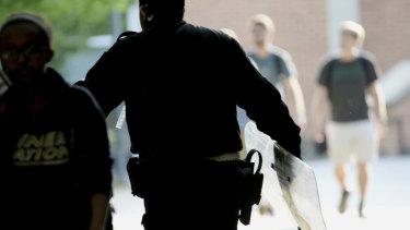A University of North Carolina, Charlotte campus police officer carries a tactical shield after a shooting in Charlotte, NC.