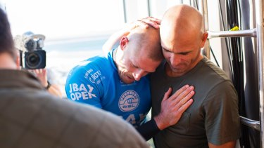 Shaken: Mick Fanning and Kelly Slater hug after Fanning's narrow escape at J-Bay.