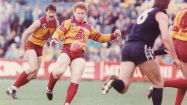 Roger Merrett (Bris) watches as teammate Brad Hardie kicks the ball in a game against Carlton in 1990.