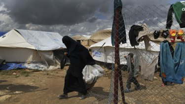 A woman walks past one of the gates of the foreign section of Al Hawl camp.